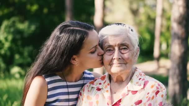 Vnučka objímá svou babičku a líbá ji na tvář
