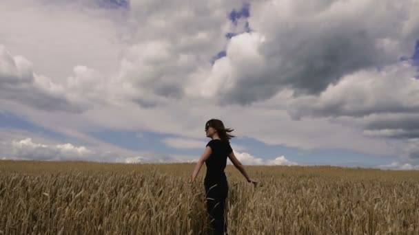 Feld. ein Mädchen geht durch ein gelbes Weizenfeld.