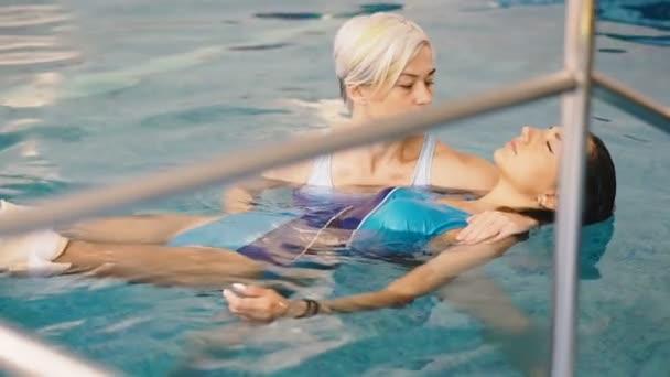 Watsu. Směr alternativní medicíny, forma terapie v teplé vodě. Mistr Watsu vede terapeutické sezení pro mladou dívku.
