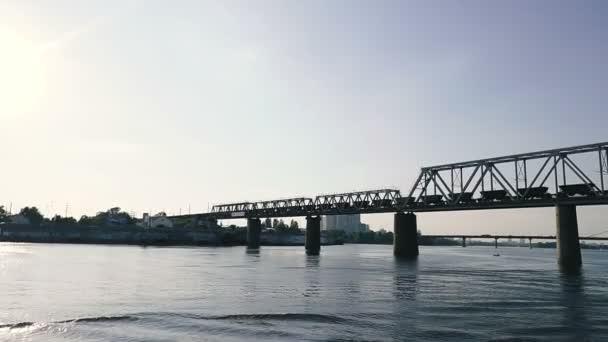 Železniční můstek. Nákladní vlak cestuje po mostě.