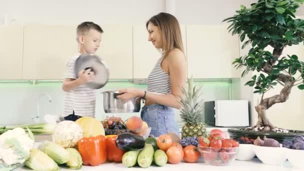 Kuchyně a jídlo. Máma a syn drží hrnec na vaření.
