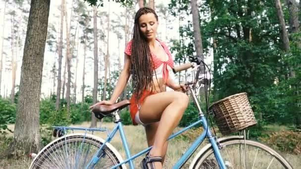 Ženské kolo. Žena stojí u ženského kola v lese.