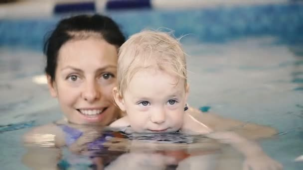 Swimming pool. Mom teaches a young child to swim in the pool.