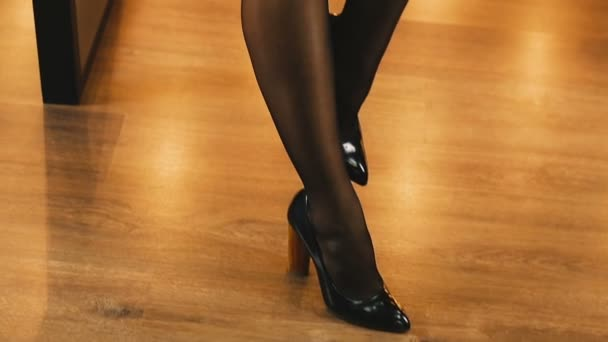 Womens legs. Womens legs are dressed in tights, high heels and a skirt.