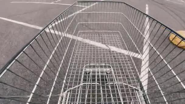 Nákupní košík. Na asfaltu jezdí prázdný nákupní košík.