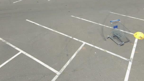 Bevásárlókocsi. Egy bevásárlókocsi áll egy üres parkolóban..