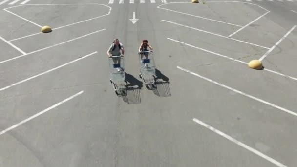 Nákupní košík. Muž a žena s nákupními vozíky běží na destilaci do obchodu.