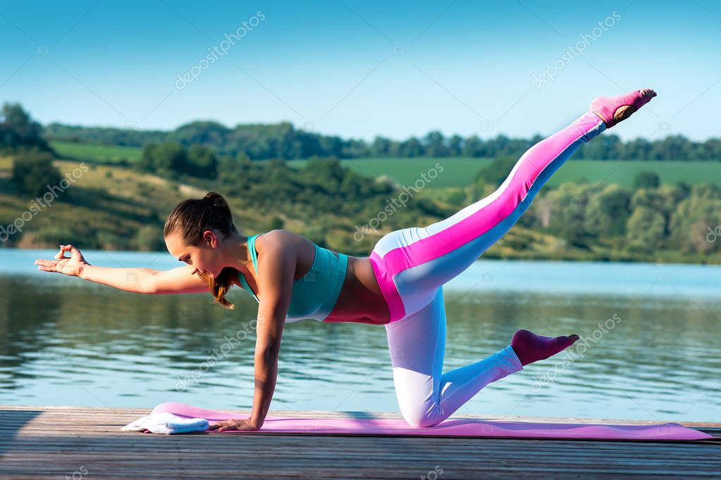Yoga.Pilates.Bird dog, chakravakasana pose. Beautiful girl practices yoga on a background of beautiful nature