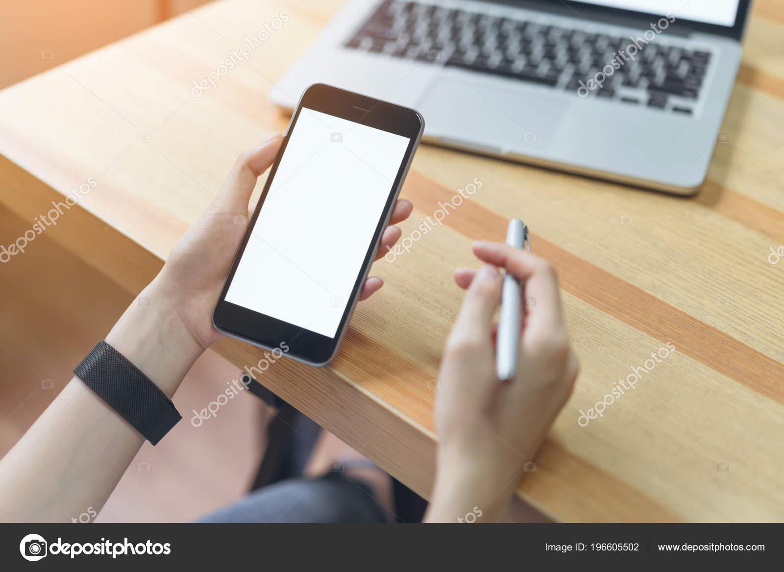 frau h lt smartphone und laptop tisch b roraum unter windows mit stockfoto kamachi 196605502. Black Bedroom Furniture Sets. Home Design Ideas