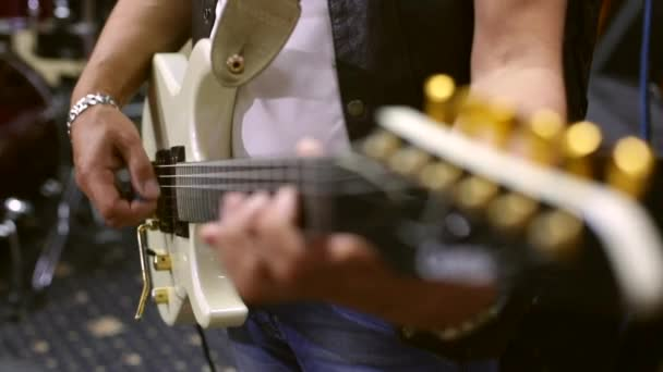 Hudebník hraje elektrickou kytaru. Close-up. Ruce mužského kolébkový na strunu kytary. Kytarista nacvičuje ve studiu. Probíhající hudební nástroj