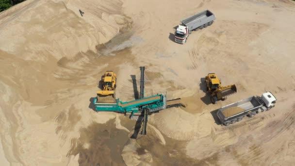Luftaufnahme beim Verladen einer Planierraupe im Steinbruch unter freiem Himmel. Sandbergbau. Bulldozer-Maschine. Planierraupe bewegt sich auf Sandmine. Bergbaumaschinen, die im Sandbruch arbeiten. Drohnen-Blick auf Bergbauausrüster
