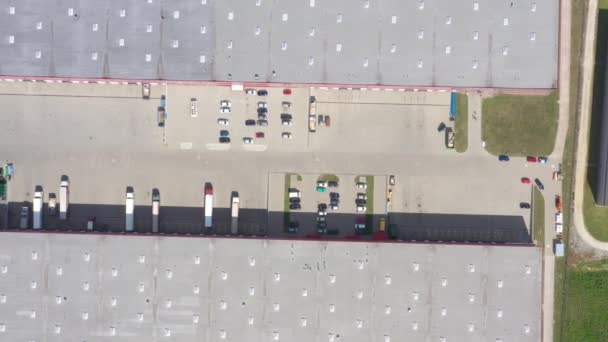Aerial Shot of Truck with Attached Semi Trailer Leaving Industrial Warehouse/ Storage Building/ Loading Area where Many Trucks Are Loading/ Unloading Merchandise
