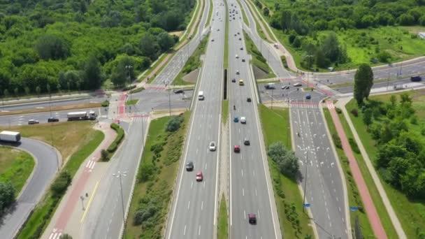 Pohled na freayskou silnici. Klip. Dálnice s provozem v lese. Příměstská dálnice s auty a náklaďáky. Cestování a doprava. Letecký pohled