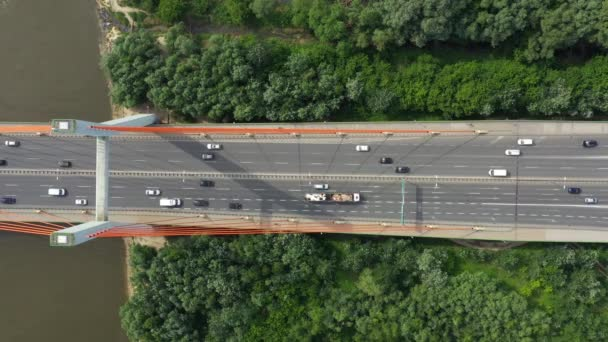City car moving at highway bridge on background smooth river surface drone view