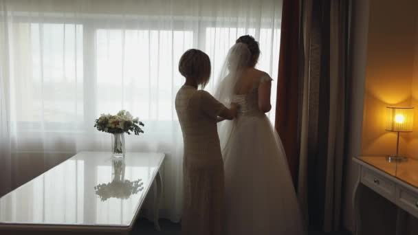 Bridesmaid helps the bride with a wedding dress