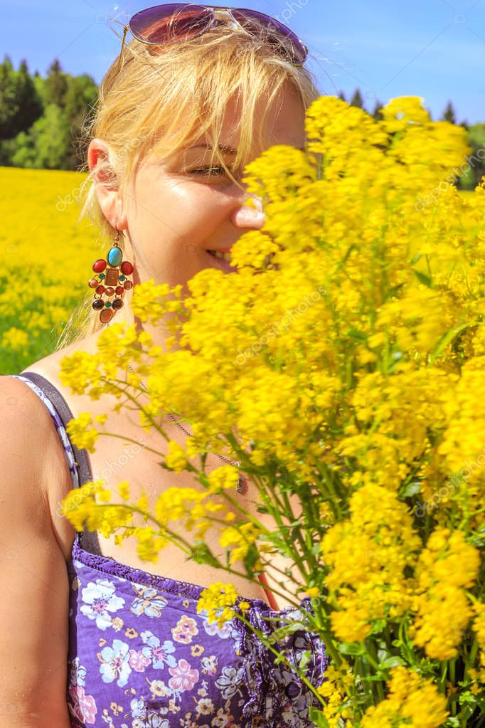 Happy blonde enjoys nature in a yellow field. Sunny day.
