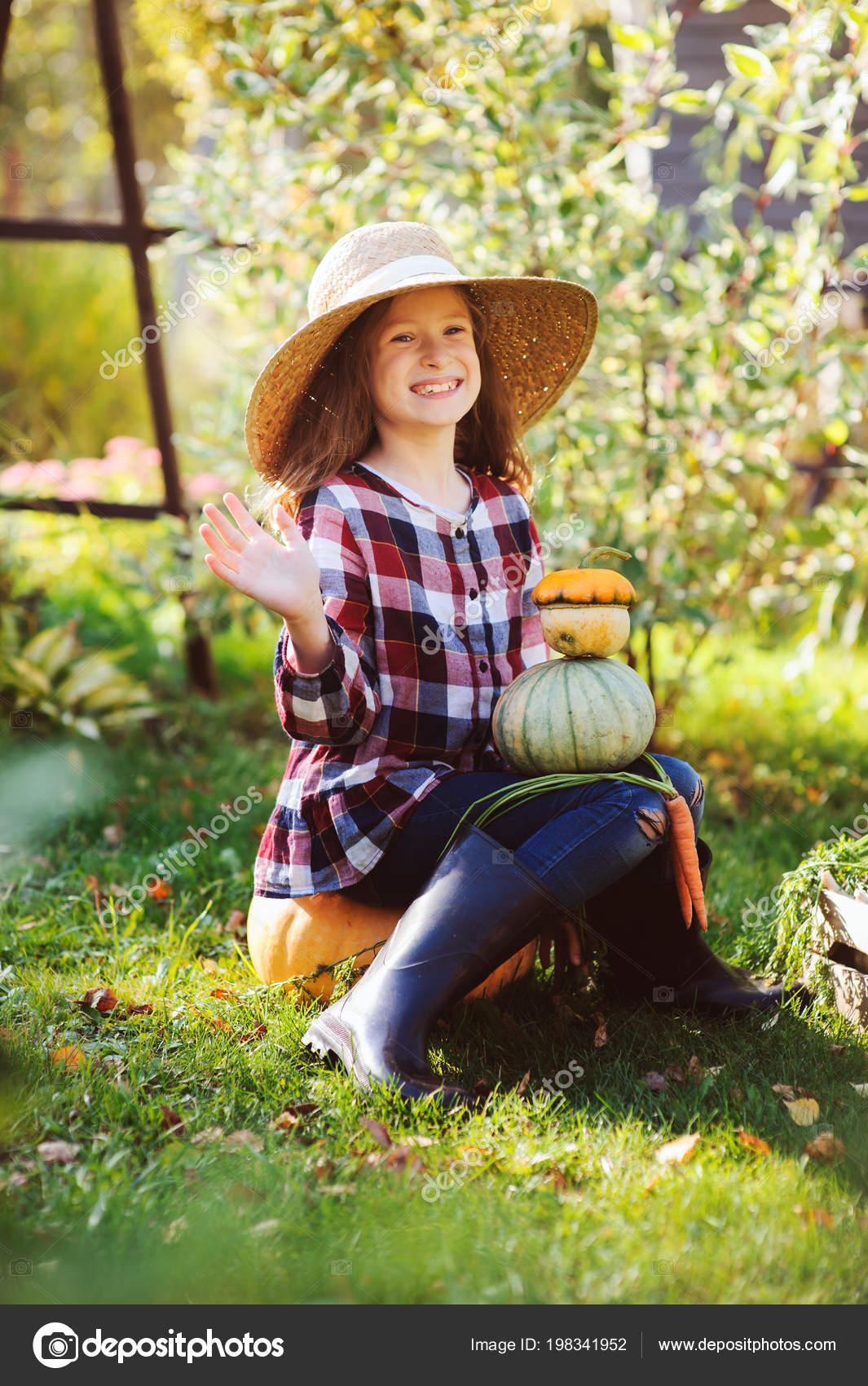 Ragazza felice del bambino divertente in cappello contadino e camicia  giocando e picking raccolto di ortaggi autunno nel giardino soleggiato. 21f3cc992875