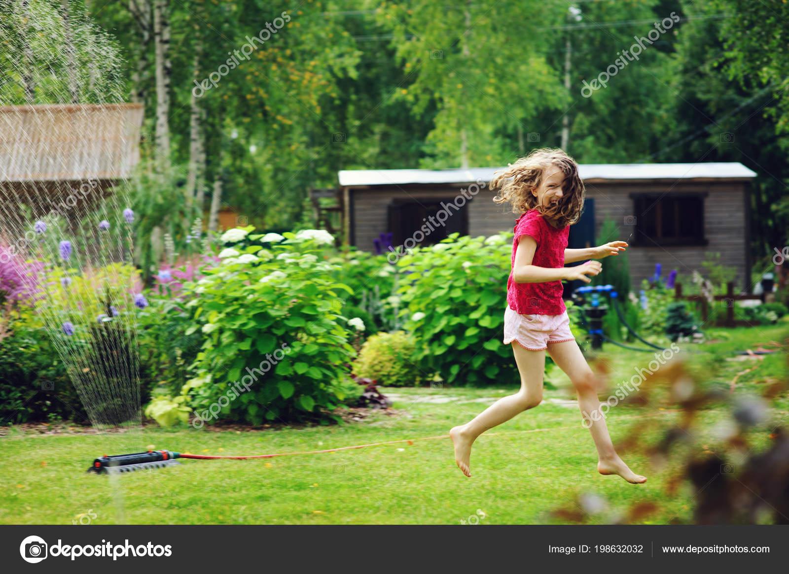Kid girl playing with garden sprinkler in hot summer day. Water outdoor  activities for children, happy childhood. 19