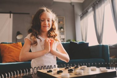 lifestyle shot of smart kid girl playing checkers at home. Board games for kids concept, candid series with real people in modern interior