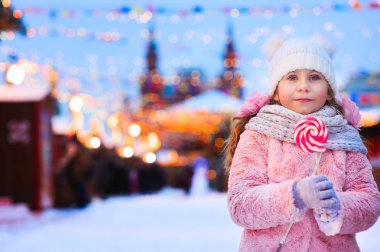 happy kid girl with christmas candy. Winter holiday portrait in the evening Moscow city with red square on background