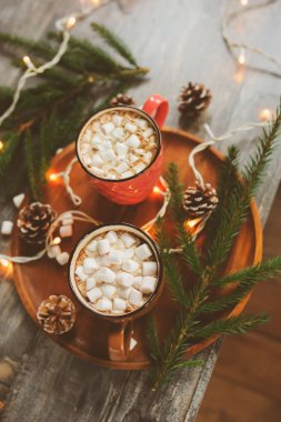 top view of hot cocoa with marshmallows on rustic wooden table with christmas lights. Cozy winter home concept