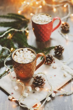 two mugs of hot cocoa with marshmallows on rustic wooden table with christmas lights. Cozy winter festive home concept
