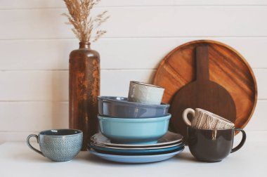 natural rustic handmade kitchenware on wooden background. Ceramic dished and cups in neutral tones, scandinavian style.
