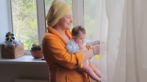 Happy Mom with baby caring for houseplants and dancing