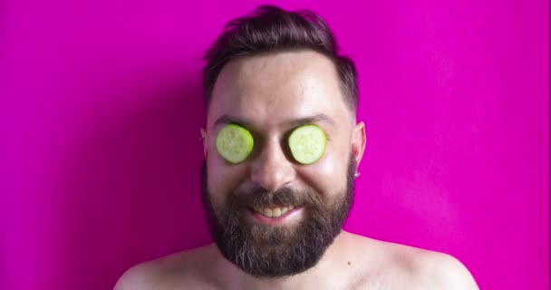 man with a beard in a spa salon gets cosmetology treatments, refreshes skin with different food mask with cucumber, tomato, strawberry, greens, cookies and dry cured sausage on face. Funny Stop motion animation