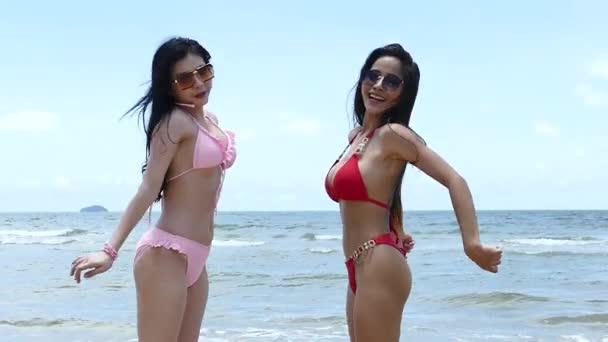 Dvě docela sexy asijské ženy šťastný hra skákání v červené a růžové bikiny se slunečními brýlemi na mořské pláži