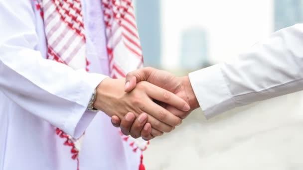 Paralaxové video Arabština a podnikatel třesoucí rukou pro úspěch korporace koncept na pozadí města krásným momentem pohybu