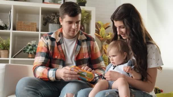 Mladý otec předvádí svou malou dceru, jak hrát s jasnou hudební hračkou