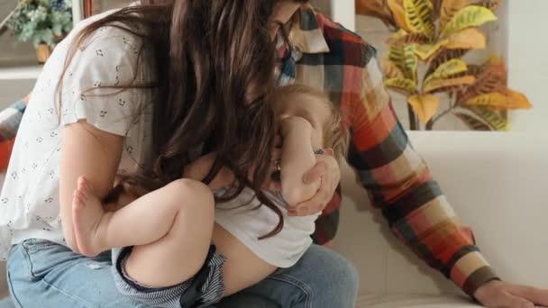Šťastné rodičovství-matka a otec si objímají malé děťátko a ukazují jí jejich lásku zpomalující pohyb