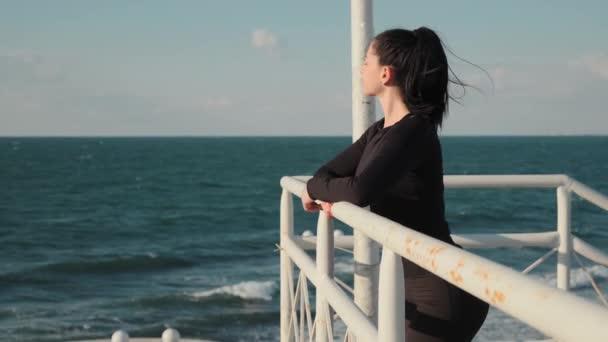 Krásná žena s dlouhými černými vlasy stojí na molu a po ránu si na moře pojí nádherný výhled do vzduchu, pomalý pohyb