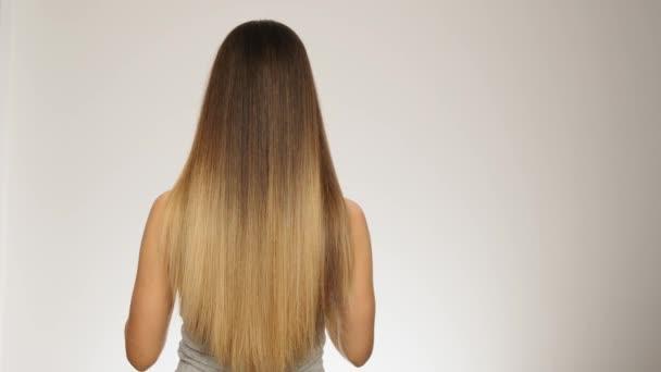 Ženský model ukazuje, že její dlouhé zdravé světlé vlasy jsou zpět vidět pomalý pohyb