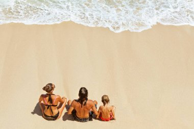 On sunny beach happy kids with parents have fun, sit on white sand see at sea surf with foam and splashes. Top view. Active children lifestyle, summer family vacation travel on tropical family resort.