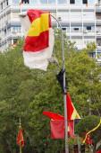 Madrid, Španělsko- 12. října 2019: Parašutista letectva, vznáší se nad městem Madridem s vlajkou Španělska přivázanou ke kotníku jedné ze svých nohou v den ozbrojených sil, visí na pouliční lampě se španělskou vlajkou