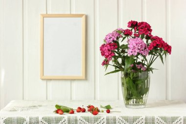 empty frame on the wall, bouquet of Turkish carnations and garden strawberries on the table. light still life in rustic style. mockup, scene creator.