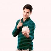Fotografie Schönen jungen Mann mit gebräunter Haut hält ein Sparschwein. Einsparungen-Konzept