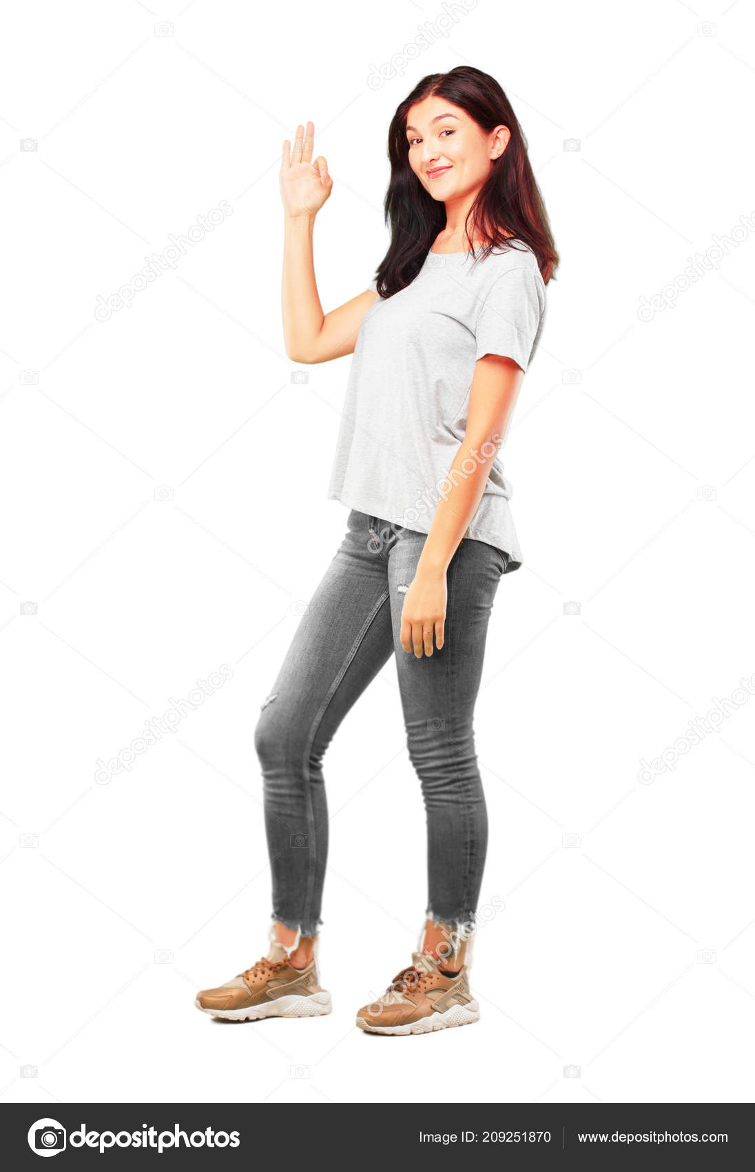 Young pretty girl full body making alright okay gesture approvingly stock photo