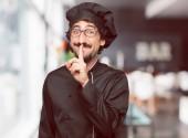 Fényképek fiatal őrült ember, mint egy szakács mutatóujját a szája, előtt mosolyogva csendet kér, vagy egy titkos megosztása