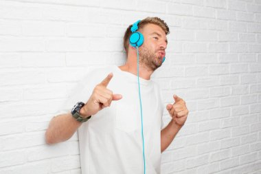 handsome blonde man listening music with a headphones