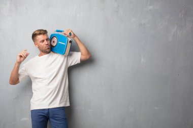 handsome blonde man listening music with a vintage radio