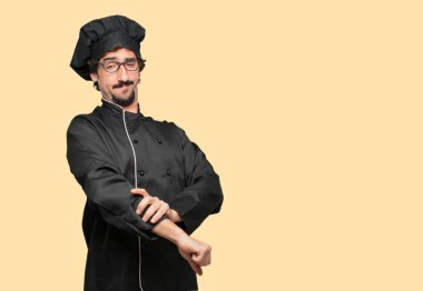 young crazy man as a chef with a proud, happy and confident expression; accepting a challenge while pulling up sleeves as if getting ready for the job, smiling and sure of success, giving an