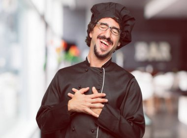 young crazy man as a chef Laughing out loud with head tilted backwards and happy, cheerful expression