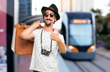 Young bearded cool traveller man with a bag. Holidays concept.