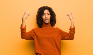 young pretty black woman celebrating an unbelievable success like a winner, looking excited and happy saying take that! against orange wall