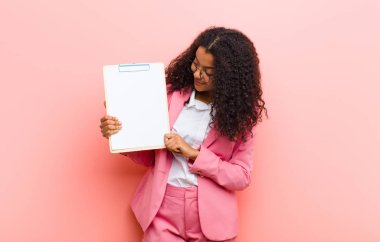 young black pretty woman with a paper sheet against pink wall background
