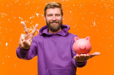 young blonde man with a piggy bank wearing a purple hoodie against damaged orange wall