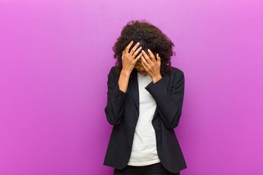 young black business woman covering eyes with hands with a sad, frustrated look of despair, crying, side view